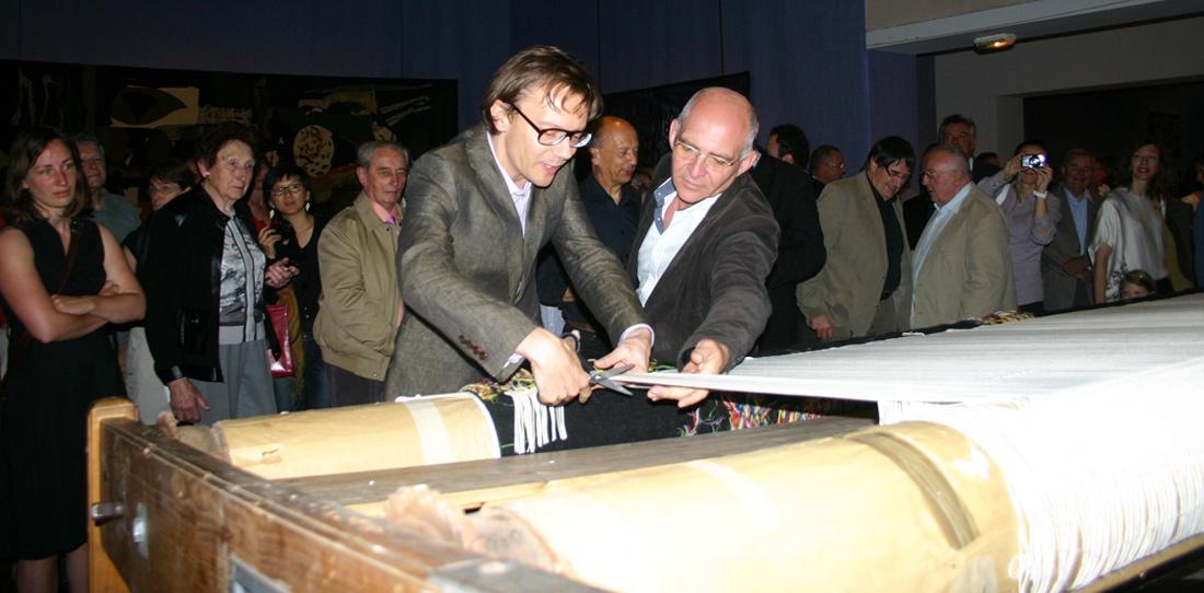 Mathieu Mercier libérant sa tapisserie Sans Titre du métier à tisser, aux côtés de Pascal Legoueix